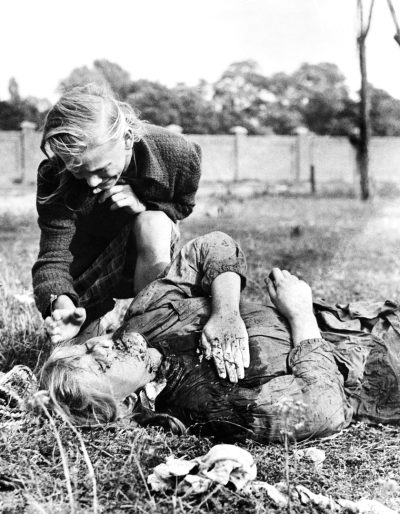 Polish 12-year-old Girl Kneeling Over The Body Of Her Sister Who Was Killed During Bombing By The Nazis, Poland On September 9, 1939.